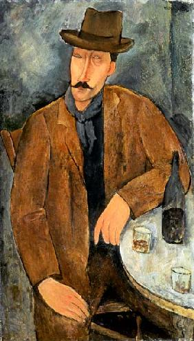 A seated man leaning on a table