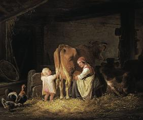 Young farmer with child when milking