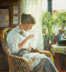 Sewing young woman at the window