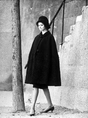 Presentation of fashion by Nina Ricci for autumn-winter 1960-1961 : black wool cape, hat