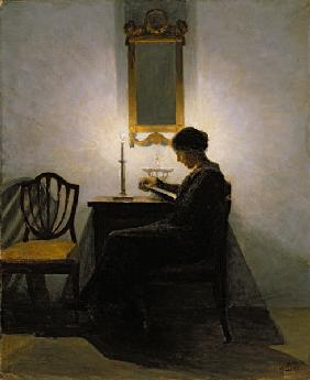 Woman reading by candlelight