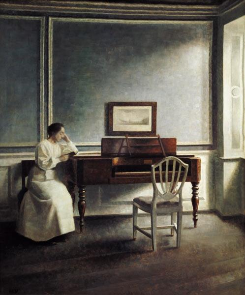 Woman, reading next to a piano in a book.